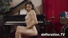 Brunetka przy fortepianie pokazuje swoje ciałko