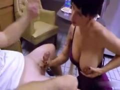 Cycata mama klęczy i zabawia się jego pałkę